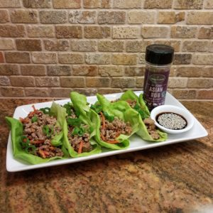 3 lettuce wraps with meat and spices in them and a side of soy sauce with seeds in it