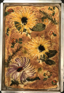 Pan of focaccia bread with vegetable flower designs